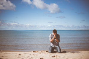man on his knees praying on the beach - addiction tests faith