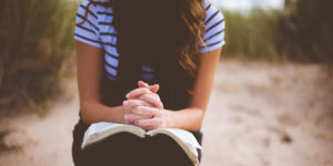 young woman with hands clasped on open bible - christian drug program