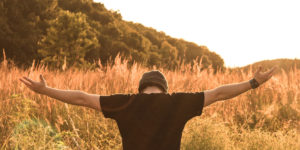 young man in field with head bowed and arms open to the sky - spiritual aspect of recovery