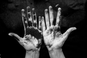looking down at palms of hands covered in dirt - black and white - stigma of addiction