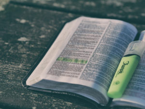 Holy Bible open with green highlighter between pages - catholic drug program