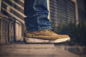 close up of tan leather sneakers standing on concrete steps -