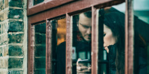 couple looking at same phone, seen through building window - codependency in addiction
