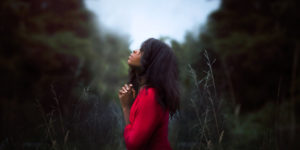 lovely African American woman in nature clasping hands together and looking skyward -