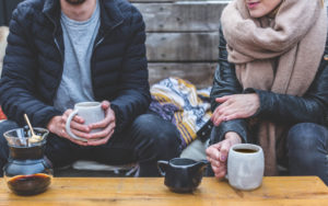 couple sitting and drinking tea outside in winter wearrebuilding trust after addiction