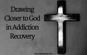 words: drawing closer to god in addiction recovery next to cross hanging on wall - black and white
