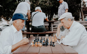 elderly gentlemen playing a game of chess in the park - alcohol abuse in the elderly