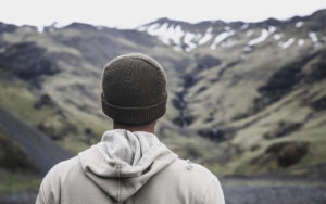young man in sock cap and hooded sweatshirt facing away from camera and looking at mountain range - cognitive behavior therapy addiction