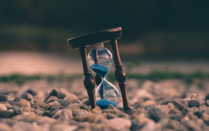 wooden hourglass with blue sand sitting in rocks