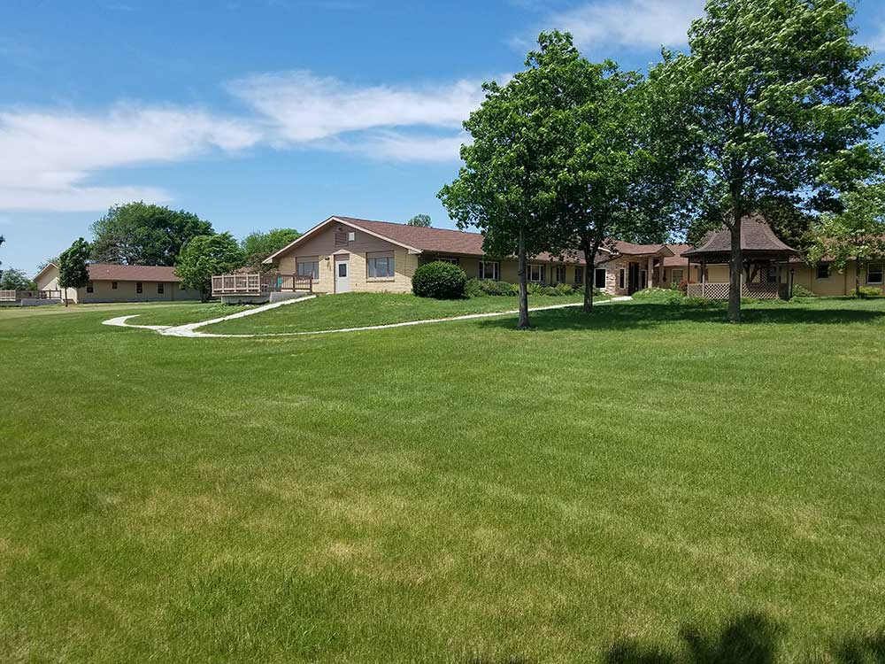 backyard of facility with green grass and trees