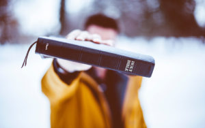 man holding black Holy Bible up into camera
