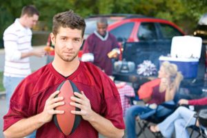 Tailgating-and-Temptation-Alcohol-Recovery-and-the-Pressure-at-Social-Events - young man holding football at tailgate party