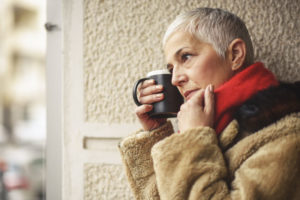lovely senior woman drinking coffee or cocoa outside during the winter