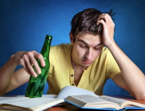 young man drinking beer while studying