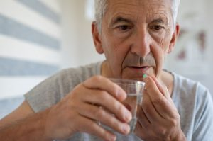 senior citizen man taking pill