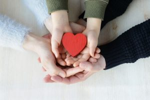 close up of hands holding heart - family