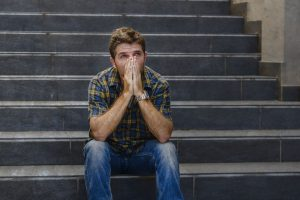 upset man sitting on stairs