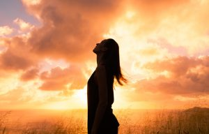 silhouette of woman looking skyward - sunset - spirituality