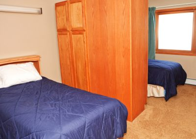 small bedroom with 2 double beds separated by wardrobe