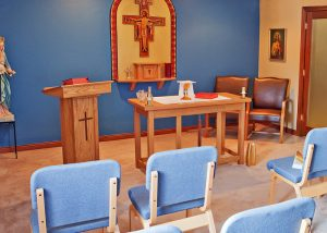 inside of Catholic church with blue walls and blue chairs