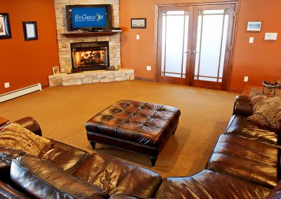 living room with tv, fireplace, and brown leather sectional