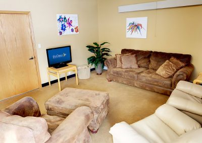 Tan room with one couch and several recliners
