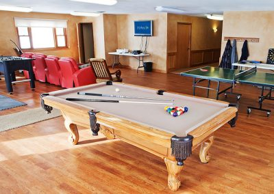 game room with pool table, table tennis, Foosball, and red recliners