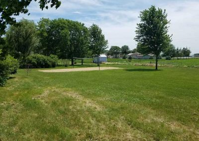 outdoors area with sand volleyball court surrounded by green trees