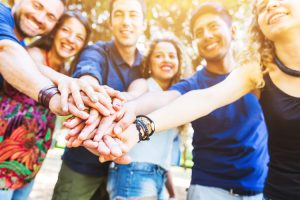 smiling group of friends with hands stacked in fellowship