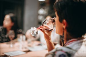 woman drinking red wine at dinner table - women