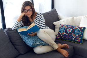 woman reading book on her couch - activities