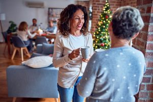 two women drinking coffee and talking at holiday gathering - the holidays