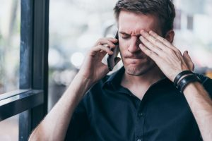 frustrated man upset talking on mobile phone - signs of relapse