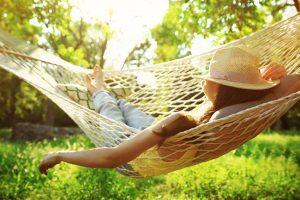 woman relaxing in backyard hammock - sober summer