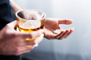 person holding glass of liquor in one hand and white pills in the other - alcohol and opioids