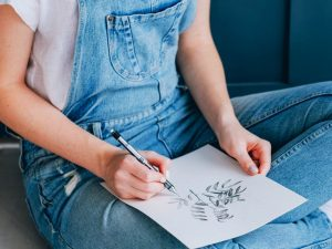 closeup of young woman sitting cross-legged, drawing with pen on paper - creativity