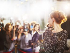 woman walking red carpet surrounded by flashing cameras and paparazzi - celebrities and addiction