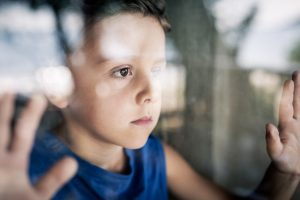 closeup of young boy looking out window with his hands on the glass, sad - children