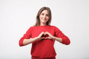 pretty young woman in red sweater making the shape of a heart over her heart