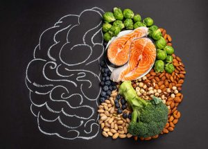 chalkboard with brain drawn on it and healthy foods laying on half of it - brain health