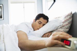 dark haired man in bed hitting snooze on alarm clock - sleep habits