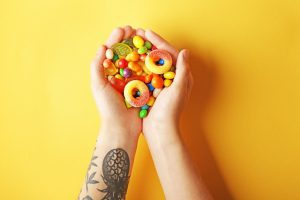 woman holding hands together that are filled with gummy candy and other candy - her arm is tattooed and the background is bright yellow - sugar cravings