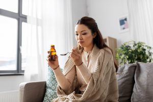 pretty Asian woman taking cold or cough syrup at home - codeine cold