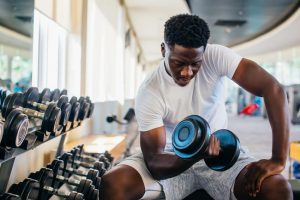 handsome young Black man lifting free weights on a bench at the gym - fit