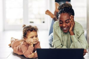 little girl and young woman looking at tablet computer together - parenting
